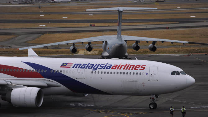 A Malaysia Airlines plane, foreground, prepares to go out onto the runway and passes by a stationary Chinese Ilyushin 76 aircraft at Perth International Airport in Perth, Australia, Tuesday, March 25, 2014. Malaysia said Tuesday that it has narrowed the search for a downed jetliner to an area the size of Texas and Oklahoma in the southern Indian Ocean, while Australia said improved weather would allow the hunt for possible debris from the plane to resume. (AP Photo/Greg Wood, Pool)