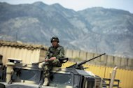 This file photo shows an Afghan soldier sitting on top of a military vehicle at a base in Khost Province, pictured on August 14, 2012. A suicide car bombing hit a US-run base in Khost on Wednesday, killing at least three Afghans and wounding seven others, according to officials