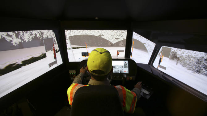 Driver Terence Mundt operates a snowplow simulator during a North Texas Tollway Authority training class in Plano, Texas, Thursday, Nov. 15, 2012.  The NTTA is using the computer generated simulator to help snowplow operators become better at handling slick roads in a region not used to ice and snow. Highway officials in at least nine states are using the sophisticated simulator to give plow drivers a chance to practice snow removal in any weather. It works like a video game, recreating slick pavement, poor visibility and even children or animals bolting across the road.(AP Photo/LM Otero)