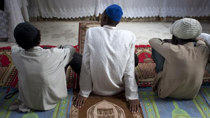 In this Sept. 28, 2012 photo, Muslim men sit on prayer rugs at the Al-Fattah Mosque during a Friday prayer service in Gressier, Haiti. Islam has won a growing number of followers in this impoverished country, especially after the catastrophic earthquake in 2010 that killed hundreds of thousands and left millions more homeless. (AP Photo/Dieu Nalio Chery)