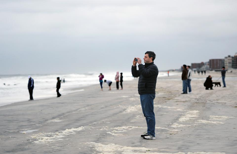People venture out during the strong winds and high surf of the Atlantic Ocean before the arrival of Hurricane Sandy on Sunday, Oct., 28, 2012, in Long Beach, N.Y. (AP Photo/Kathy Kmonicek)