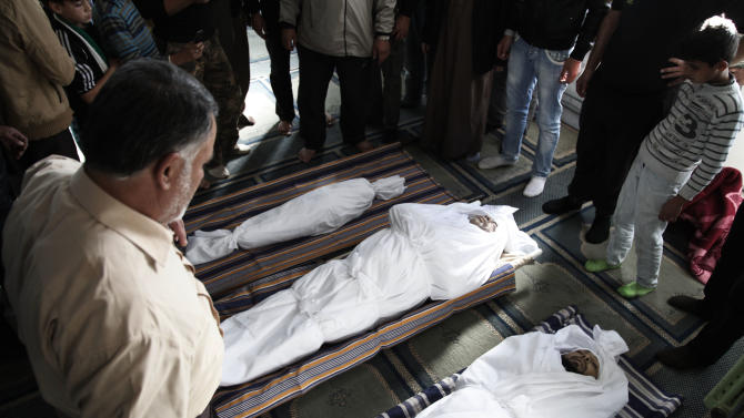 Syrians and Jordanians look at the bodies of, Emara al-Zoabi, 7 months, left, Moath al-Rawashdy, 30 years, right, and Ahmed al Natoor, 62 years, center, who were killed from Syrian government forces shelling in Ramtha City, north Amman, Jordan, Sunday, Dec. 2, 2012. They were killed in Tafas village, in the Syrian city of Daraa, on Dec. 1, 2012. Syrian refugees, who crossed the border into Jordan last night from Tafas village, Daraa, tried to rescue the three victims, as they smuggled them into Jordan, but they died on the way. (AP Photo/Mohammad Hannon)