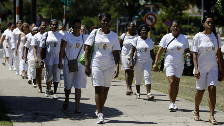 Members of dissident group Ladies in White take part in their weekly march in front of Santa Rita church in Havana, Cuba, Sunday March 18, 2012.  Dissident Angel Moya says police detained his wife Bertha Soler and three dozen supporters of the Ladies in White dissident group on Sunday morning. The detentions come just over a week ahead of a visit by Pope Benedict XVI, who is likely to bring up the issue of religious, political and human rights during his tour. The image of the woman on their shirts is of Laura Pollan, the group's former leader who died in 2011 of a heart attack. (AP Photo/Franklin Reyes)
