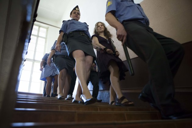 Feminist punk group Pussy Riot member Maria Alekhina, escorted to a court room in Moscow, Russia, Wednesday, Aug. 8, 2012. Prosecutors on Tuesday called for three-year prison sentences for feminist punk rockers who gave an impromptu performance in Moscow's main cathedral to call for an end to Vladimir Putin's rule, in a case that has caused international outrage and split Russian society.(AP Photo/Alexander Zemlianichenko)