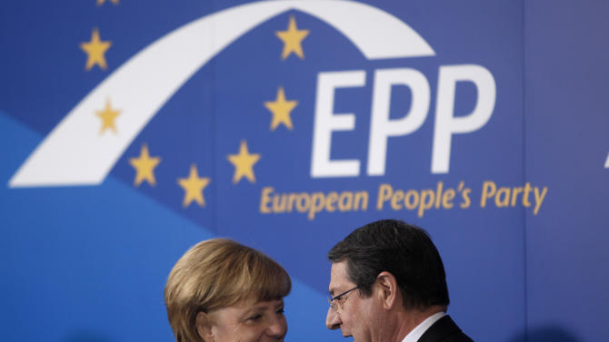 German Chancellor Angela Merkel talks with Cyprus' main opposition Democratic Rally party leader Nicos Anastasiades, right, following a European People's Party (EEP) meeting in Cyprus' southern coastal resort of Limassol in an extraordinary summit on Friday, Jan. 11, 2013. Among the topics of discussion at the meeting hosted by the leader of Cyprus' main opposition Democratic Rally party Nicos Anastasiades will be the EU budget. Anastasiades is currently leading opinion polls as the top contender ahead of the country's Feb. 17 presidential election. Cyprus is in the midst of talks with international lenders on a bailout to rescue its ailing banking sector that sustained massive losses on bad Greek debt and loans. (AP Photo/Petros Karadjias)