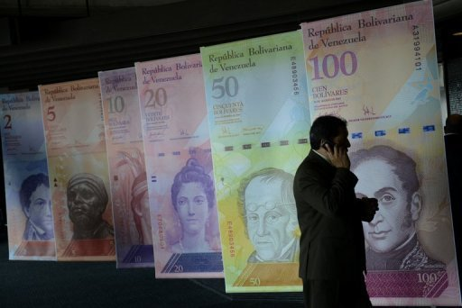 Posters depicting Venezuelan bolivares currency notes in Caracas last August. Ailing Venezuela President Hugo Chavez's absence has left on indefinite hold major economic issues, including a long-awaited currency devaluation, in the top oil exporter, analysts said Wednesday.