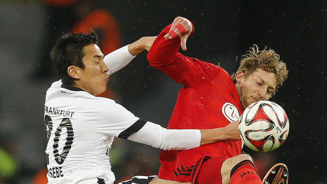 Frankfurt's Makoto Hasebe from Japan, left, and Leverkusen's Stefan Kießling challenge for the ball during the German first division Bundesliga soccer match between Bayer 04 Leverkusen and Eintracht Frankfurt in Leverkusen, Germany, Saturday, Dec. 20, 2014. (AP Photo/Frank Augstein)