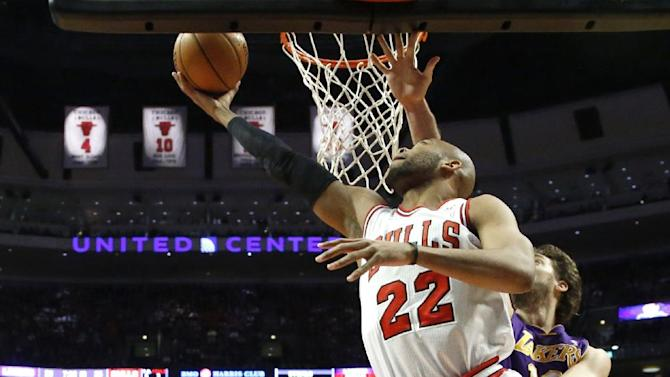 Chicago Bulls forward Taj Gibson (22) shoots a reverse layup past Los Angeles Lakers forward Pau Gasol as Bulls' Nazr Mohammed (48) watches during the first half of an NBA basketball game, Monday, Jan. 21, 2013, in Chicago. (AP Photo/Charles Rex Arbogast)