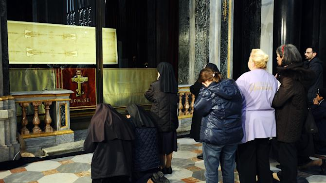 """Faithful pray in front of the Shroud of Turin that went on display for a special TV appearance Saturday, March 30, 2013. The Shroud went on display amid new research disputing claims it's a medieval fake and purporting to date the linen some say was Jesus' burial cloth to around the time of his death. Pope Francis sent a special video message to the event in Turin's cathedral, but made no claim that the image on the shroud of a man with wounds similar to those suffered by Christ was really that of Jesus. He called the cloth an """"icon,"""" not a relic — an important distinction. """"This image, impressed upon the cloth, speaks to our heart and moves us to climb the hill of Calvary, to look upon the wood of the Cross, and to immerse ourselves in the eloquent silence of love,"""" he said. (AP Photo/Alessandro Di Marco, Pool)"""