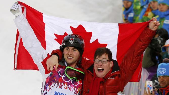 Winner Canada's Alex Bilodeau and his brother Frederic celebrate with Canadian flag after men's freestyle skiing moguls competition at the 2014 Sochi Winter Olympic Games in Rosa Khutor