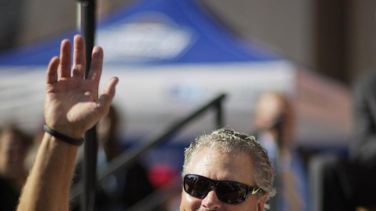 Former University of California and Atlanta Falcon quarterback Steve Bartkowski waves during an introduction at a ceremony to open the new College Football Hall of Fame, Saturday, Aug. 23, 2014, in Atlanta. The new high-tech hall features an interactive experience that begins when the guest registers for a smart pass, selects a favorite school and then sees that school's helmet illuminated