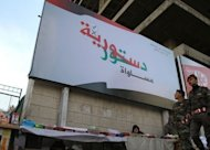 "<p>Syrian soldiers walk past a billboard reading in Arabic text ""Syria Constitution.. equality"" in Damascus on February 23. Rebel forces and Syrian army units were locked in fierce clashes around elite Republican Guard posts in the suburbs of Damascus on Tuesday, a monitoring group said.</p>"