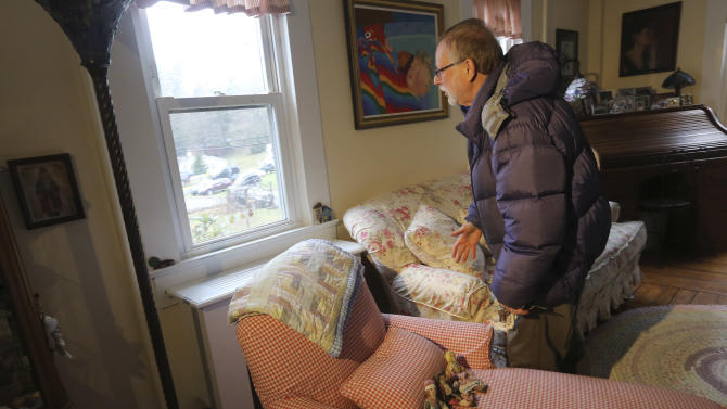 Gene Rosen looks out a window in his home that one of the children was looking out of during an interview with the Associated Press, Monday,Dec. 17, 2012 in Newtown, Conn. On the day of the shooting, Rosen took in four girls and two boys that were sitting at the end of his driveway; they had just run from the school, among the first to escape Friday's deadly shooting. He ran upstairs and grabbed an armful of stuffed animals he kept there. He gave those to the children, along with some fruit juice and sat with them as the two boys described seeing their teacher being shot. (AP Photo/Mary Altaffer)