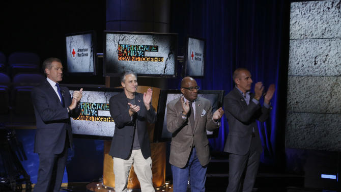 "In this photo provided by NBC, Brian Williams, Jon Stewart, Al Roker and Matt Lauer applaud during ""Hurricane Sandy: Coming Together"" Friday, Nov. 2, 2012, in New York. Hosted by Matt Lauer, the event is heavy on stars identified with New Jersey and the New York metropolitan area, which took the brunt of this week's deadly storm. (AP Photo/NBC, Heidi Gutman)"