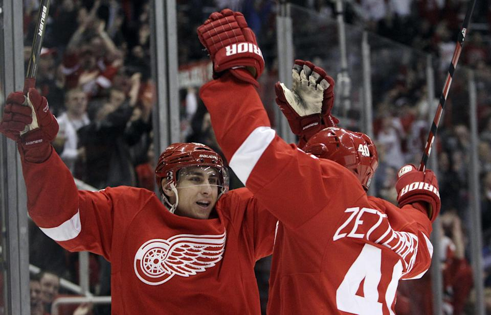 Detroit Red Wings center Valtteri Filppula (51), of Finland, celebrates with teammate Henrik Zetterberg's goal against San Jose Sharks goalie Antti Niemi during the first period of an NHL hockey game in Detroit, Sunday, Feb. 19, 2012. (AP Photo/Carlos Osorio)