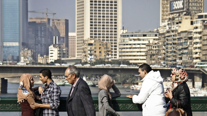 """Egyptian couples, left, talk as they enjoy the view of the Nile river on a bridge leading to Tahrir Square, in Cairo, Egypt, Sunday, Dec. 16, 2012. Key Egyptian rights groups called Sunday for a repeat of the first round of the constitutional referendum, alleging the vote was marred by widespread violations. Islamists who back the disputed charter claimed they were in the lead with a majority of """"yes"""" votes. (AP Photo/Amr Nabil)"""