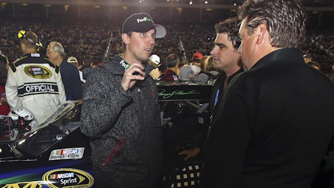 Denny Hamlin, left, talks to crew members before the NASCAR Bank of America 500 Sprint Cup series auto race in Concord, N.C., Saturday, Oct. 13, 2012. (AP Photo/Bob Jordan)