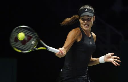 Ana Ivanovic of Serbia hits a return to Simona Halep of Romania during their WTA Finals singles tennis match at the Singapore Indoor Stadium