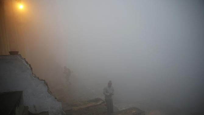 A man stands on the stairs on the banks of the river Yamuna on a cold and foggy morning in New Delhi