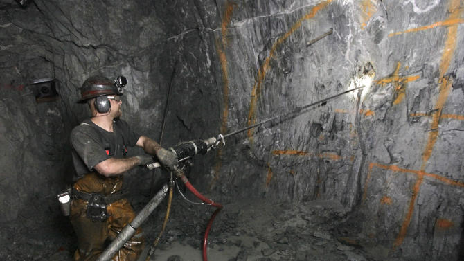 In this photo taken Thursday, Dec. 13, 2012,  miner  Keith Emerald uses a pneumatic drill to drill holes that will be packed with explosives to blast into the sold rock wall  at the Sutter Gold Mining Co's mines near in Sutter Creek, Calif.  The company announced Monday, Dec. 17, 2012, that it poured its first gold as it prepared to begin the first large scale Sierra Nevada underground gold mining in a half century. (AP Photo/Rich Pedroncelli)
