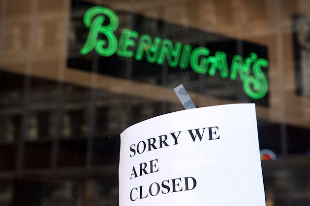 A closed sign hangs on the door of a Bennigan's Grill & Tavern restaurant.