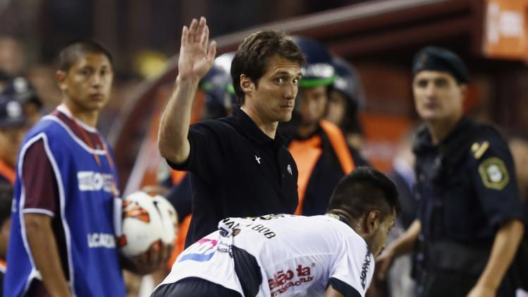 Schelotto, head coach of Argentina's Lanus, gestures to linesman next to Fernando Silva of Brazil's Ponte Preta during their Copa Sudamericana second leg final soccer match in Buenos Aires