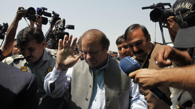 Pakistan's incoming prime minister, Nawaz Sharif, center, surround by media persons, arrives to attend the first National Assembly session in Islamabad, Pakistan, Saturday, June 1, 2013. Newly elected members of Pakistan's National Assembly were sworn in Saturday, officially marking the first transition of power between democratically elected civilian governments in the nearly 66-year history of this coup-prone country. (AP Photo/Anjum Naveed)