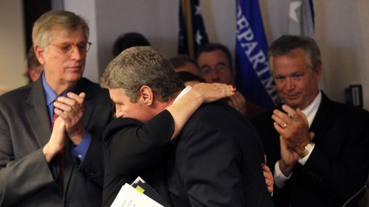 Jim Letten, U.S. Attorney for the Eastern District, hugs his wife JoAnn as he announces his resignation during a news conference in New Orleans, Thursday, Dec. 6, 2012.  Letten said his resignation is effective Dec. 11 and that he plans to stay on with the department briefly to help with the transition in leadership. (AP Photo/Gerald Herbert)