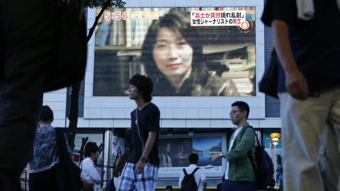 """FILE - In this Aug. 21, 2012 file photo, an image of Japanese journalist Mika Yamamoto is shown on a large monitor screen in Tokyo Tuesday, Aug. 21, 2012 during a TV news broadcast reporting her death in Syria. A press freedom advocacy group said Wednesday, Feb. 12, 2014, that the past two years have been """"absolutely atrocious"""" for the killing and imprisonment of journalists, with Syria the deadliest place to work and Turkey the number one jailer. At the launch of its annual report on """"Attacks on the Press,"""" the Committee to Protect Journalists said wide-ranging government surveillance, the unchecked murder of journalists and indirect political and commercial pressures on the media are major threats to press freedom.(AP Photo/Itsuo Inouye)"""