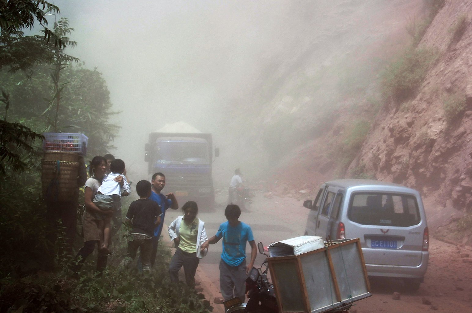 People run as rocks fall near their vehicles after the area was hit by an earthquake in Zhaotong town, Yiliang County, southwest China's Yunnan Province, Friday, Sept. 7, 2012. A series of earthquakes collapsed houses and triggered landslides Friday in a remote mountainous part of southwestern China where damage was preventing rescues and communications were disrupted. Dozens of deaths have been reported.