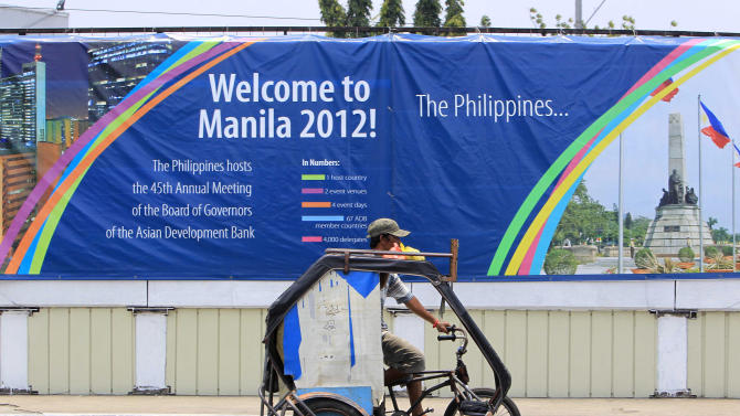 """A resident pedals his tricycle, locally known as """"pedicab"""", past a wall covered with a tarpaulin poster of the ongoing 45th Annual Board of Governors meeting of the Asian Development Bank at suburban Pasay city south of Manila, Philippines, Thursday May 3, 2012. Delegates attending the international conference of the ADB in the Philippines capital may not see what they came to discuss: abject poverty. The makeshift, temporary wall on both sides of the bridge from the airport to downtown Manila, hides a sprawling slum along a garbage-strewn creek. (AP Photo/Bullit Marquez)"""