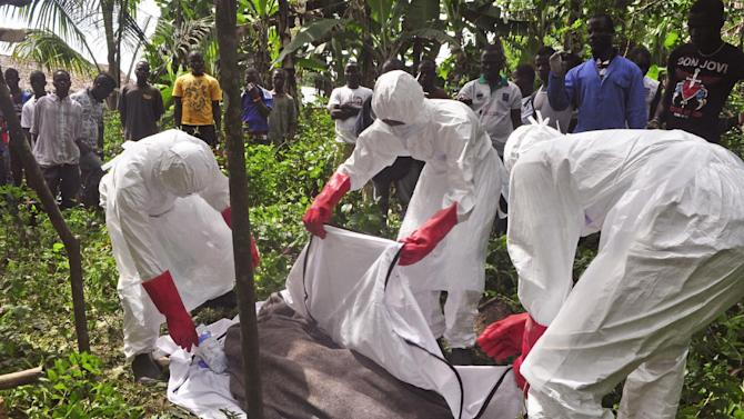 Hearth workers cover the body of a man suspected of dying from the Ebola virus on the outskirts of Monrovia, Liberia, Friday, Oct. 31, 2014. The World Health Organization said this week that the rate of infection in Liberia appears to be falling but warned that the response effort must be kept up or the trend could be reversed. (AP Photo/ Abbas Dulleh)