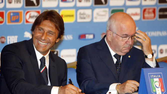 Italian national soccer team's new coach Antonio Conte, left, flanked by Italian Soccer Federation (FIGC) President Carlo Tavecchio, poses for photographers as he finalizes his contract prior to the start of the press conference for his presentation, in Rome, Tuesday, Aug. 19, 2014. (AP Photo/Riccardo De Luca)