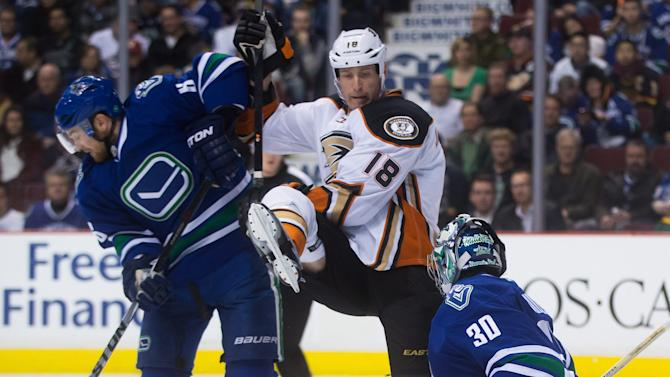 Anaheim Ducks' Tim Jackman (18) tries to avoid the puck while being checked by Vancouver Canucks' Yannick Weber, left, of Switzerland, in front of goalie Ryan Miller during the first period of an NHL hockey game Tuesday, Jan. 27, 2015, in Vancouver, British Columbia. (AP Photo/The Canadian Press, Darryl Dyck)