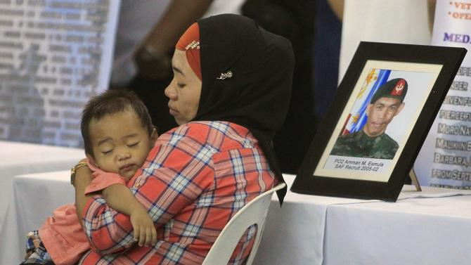 A relative carries her son while taking a rest beside the picture of her loved one, one of the slain member of the Special Action Force (SAF) who were killed in Sunday's clash with Muslim rebels, during a service inside a police headquarters in Taguig city
