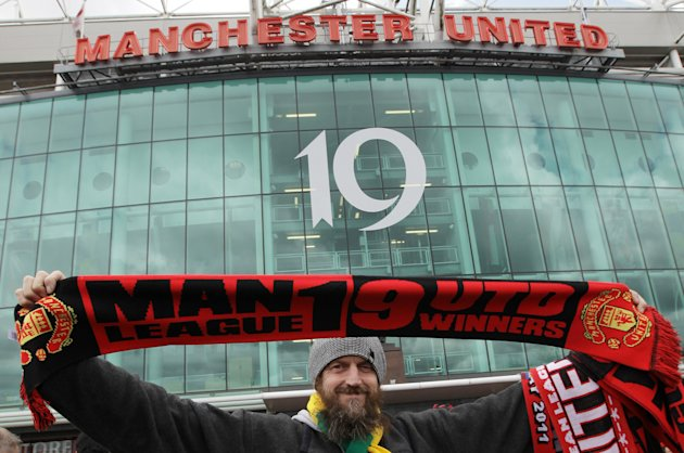 FILE - In this May 22, 2011 file photo, a Manchester United fan holds up a scarf displaying Manchester United's 19 league titles ahead of the English Premier League soccer match between Manchester United and Blackpool at Old Trafford in Manchester, England. Manchester United is readying for its debut on the New York Stock Exchange on Friday. The 134-year-old soccer club, with a record 19 English championships, is one of the most well-known teams on the planet, so the IPO is highly anticipated. But some analysts say the debt-ridden team is overvalued and the offering is dependent on investors wearing their fan caps rather than their financial caps. (AP Photo/Jon Super, File)