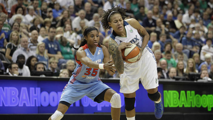 Minnesota Lynx guard Seimone Augustus, right, protects the ball against Atlanta Dream guard Angel McCoughtry (35) in the first half of Game 2 of the WNBA Finals basketball series, Wednesday, Oct. 5, 2011, in Minneapolis. (AP Photo/Stacy Bengs)