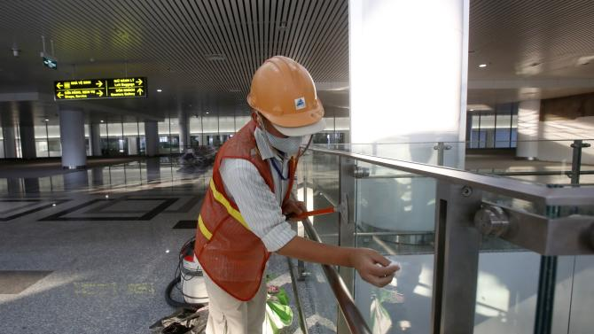 A worker cleans glass panels ahead the opening of the new terminal two wing at Noi Bai international airport in Hanoi