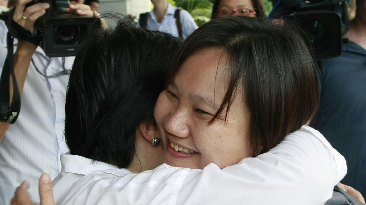 Chiranuch Premchaiporn, right, director of Thai newspaper website Prachatai, is greeted by an unidentified friend upon her arrival at the criminal court Monday, April 30, 2012, in Bangkok, Thailand. A Thai judge postponed a verdict that had been expected Monday for Chiranuch, the webmaster accused of failing to act quickly enough to remove Internet posts deemed insulting to Thailand's royalty.  (AP Photo/Apichart Weerawong)