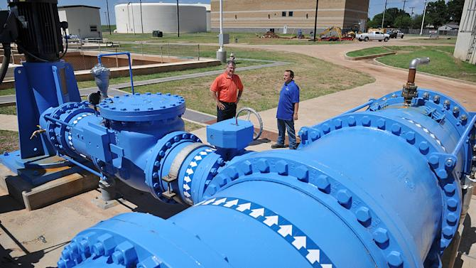 City of Wichita Falls Utilities Operations Manager Daniel Nix, left, and Nolan Mulholland, a water plant operator, look over the massive pumps and plumbing system Monday, July 7, 2014, which can move up to 10 million gallons a day from the filtration plant to a ground storage tank at the Cypress Water Treatment Plant. The city's Direct Potable Reuse plan will go online this week recycling treated wastewater through the community water system, saving approximately 5 million gallons per day that would have been drawn from the reservoirs. (AP Photo/Wichita Falls Times Record News, Torin Halsey)