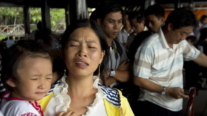 Pham Thi Hoang, second from left, cries while waiting for her missing son Pham Xuan Khanh, 9, who was aboard a tourism boat which sank in Saigon River, Binh Duong province, Vietnam, Saturday, May 21, 2011. A little boy's birthday party went tragically wrong Friday when the double-decker tour boat capsized during a storm, killing 15 people, including the 3-year-old being honored and four other children, officials said Saturday. (AP Photo)