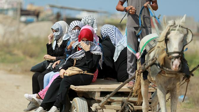 Female Palestinian protesters ride a horse cart on their way to clashes with Israeli troops near the Israeli border fence in the east of Gaza City