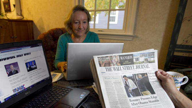 "This photo taken Oct. 5, 2012 shows independent voters Thyra and Joe Galli reading up on political news on Internet and with print newspapers at their home in Portsmouth, N.H. Thyra plans to vote for Obama and Joe is supporting Romney. New Hampshire's nickname is ""the Granite State"" but there's nothing solid about its political landscape. Independent voters have been the reason in recent presidential elections. Today, former factory towns to the south _ Manchester and Nashua _ typically vote Republican as do the rural small towns up north, while state capital Concord and university towns like Durham, Dover, Keene and Hanover tend to lean Democratic. And the entire state is peppered with independents like Joe and Thyra Galli of Portsmouth. (AP Photo/Robert F. Bukaty)"