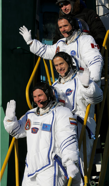 U.S. astronaut Thomas Marshburn, center, Russian cosmonaut Roman Romanenko, bottom, and Canadian astronaut Chris Hadfield, crew members of the mission to the International Space Station, gesture prior