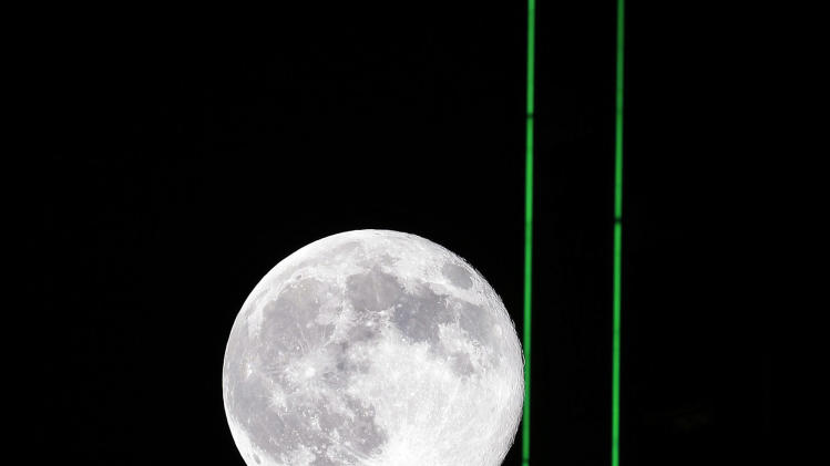 A supermoon moves across the sky behind the neon green lights of the Bank of America Tower in downtown Dallas, Saturday, July 12, 2014. (AP Photo/LM Otero)