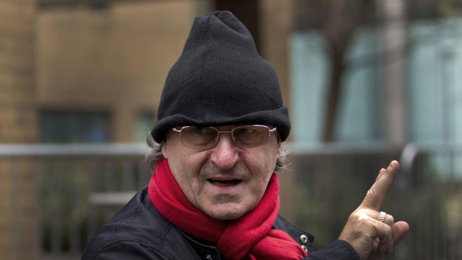 """FILE - A Monday, Jan. 30, 2012 photo from files showing Giovanni Di Stefano gesturing to photographers as he leaves Southwark Crown Court in London, after attending a bail hearing for fraud. The flamboyant but unqualified lawyer whose clients included deposed Iraqi leader Saddam Hussein has been sentenced to 14 years in jail for fraud Thursday, March 28, 2013. Giovanni Di Stefano was nicknamed """"The Devil's Advocate"""" for speaking on behalf of figures including Saddam, former Iraqi Vice President Tariq Aziz and British train robber Ronnie Biggs. Prosecutors say he conned clients out of millions of pounds by operating as a lawyer when he had no legal qualifications and was not registered to practice in Britain or Italy, where he had offices. (AP Photo/Matt Dunham, File)"""