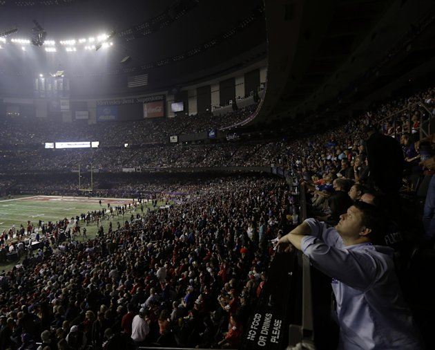 A fan looks around the Superdome after half the lights went out during a power outage in the second half of the NFL Super Bowl XLVII football game between the San Francisco 49ers and Baltimore Ravens