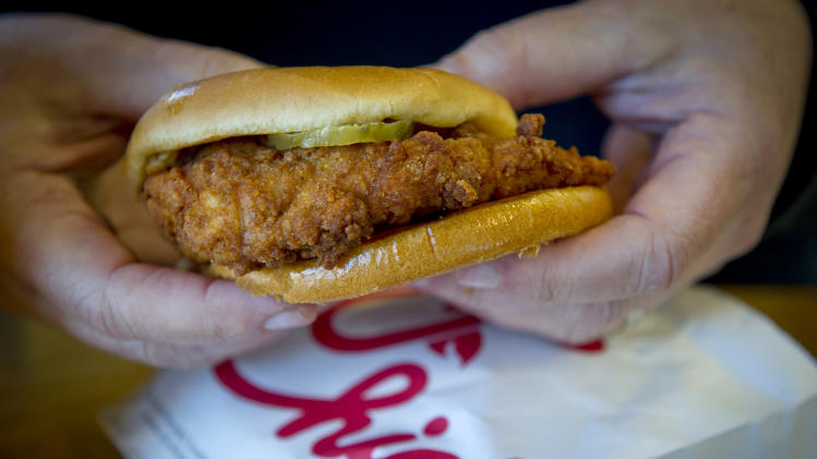 A customer holds a chicken sandwich at a Chick-Fil-A in Decatur, Ga.