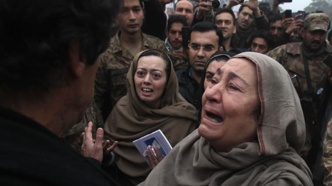 Grandmother and mother of Muhammad Ali Khan, a student who was killed during an attack by Taliban gunmen on Army Public School, react during a visit by Khan, chairman of Pakistan Tehrik-e-Insaf political party, at the school in Peshawar