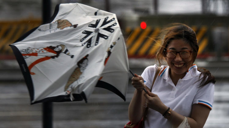A woman reacts upon her umbrella was damaged by strong winds from an approaching typhoon in Taipei, Taiwan, Wednesday, Aug. 1, 2012. Torrential rains from Typhoon Saola battered eastern Taiwan on Wednesday after killing at least 14 people and displacing 154,000 in the Philippines. (AP Photo/Wally Santana)
